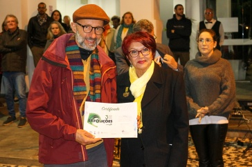 Recebendo o certificado da exposição das mãos da historiadora e Diretora do Patrimônio Histórico e Museológico, Sueli Petry.